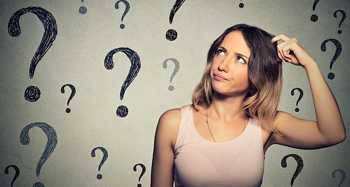Thinking young woman looking up at many question marks isolated on gray wall background